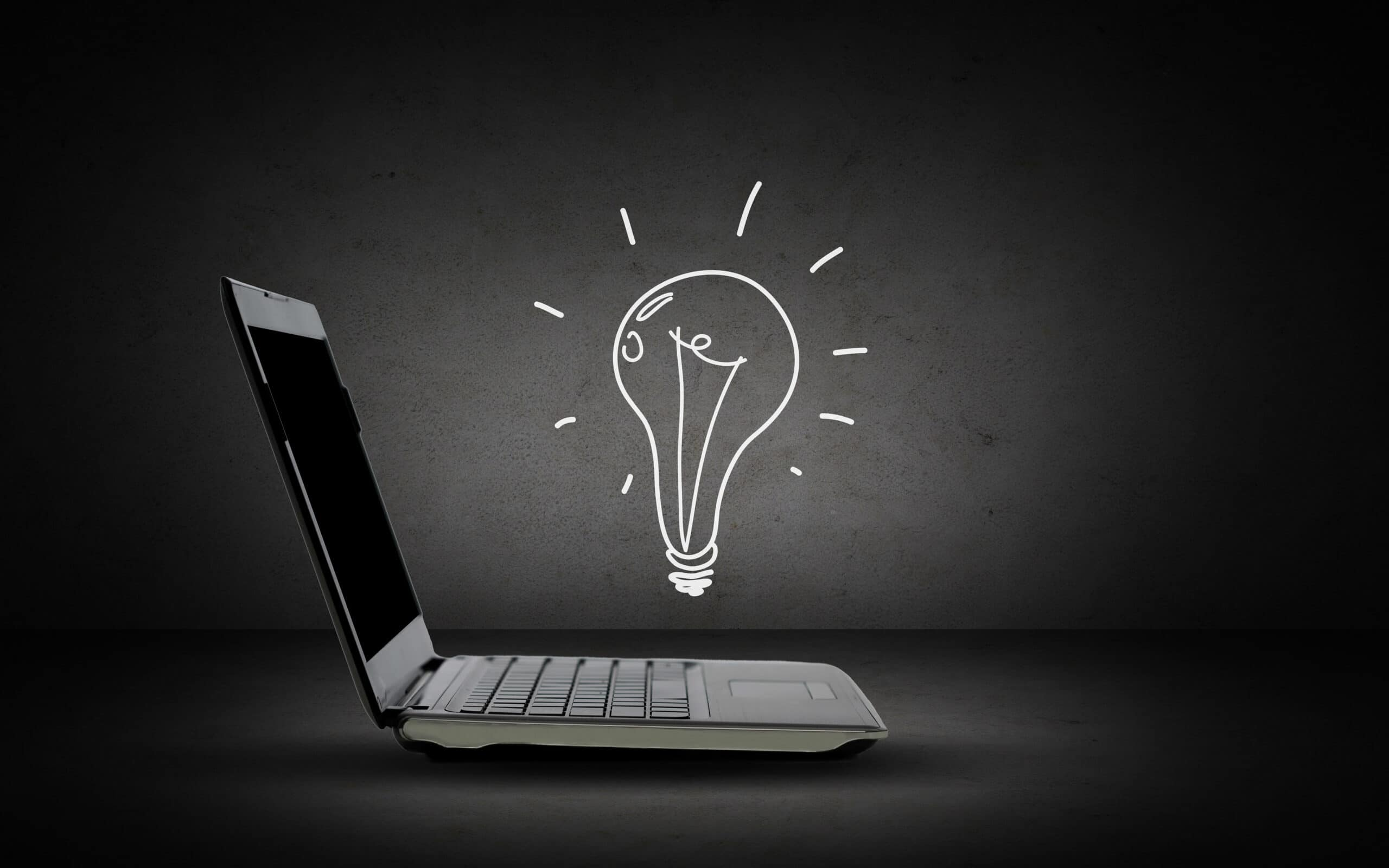 technology, business, start up and idea concept - open laptop computer with lighting bulb doodle over dark gray background